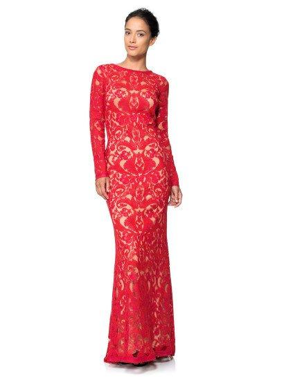 Закрытое вечернее платье прямого кроя с элегантной юбкой длиной в пол сочетает в одном образе теплый бежевый оттенок подкладки и насыщенный алый цвет кружева, покрывающего платье по всей длине и, благодаря крупному выразительному рисунку, позволяющего лаконичному крою с округлым вырезом под горло стать ярче и соблазнительнее.  Длинные рукава прямого кроя выполнены из кружевной ткани на прозрачной основе.