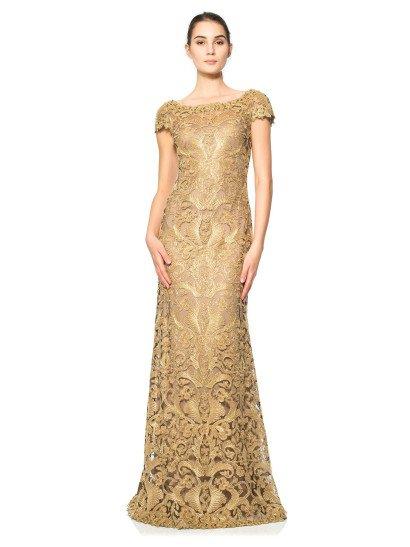 Роскошное вечернее платье прямого кроя по всей длине покрыто золотым кружевным рисунком, преображающим лаконичный бежевый оттенок ткани подкладки. Особенно притягательно такой декор смотрится на юбке, которой ажурные линии абстрактного мотива придают сдержанный объем. Верх с округлым декольте и короткими прямыми рукавами с фигурным краем женственно и стильно подчеркивает фигуру, не делая броских акцентов.