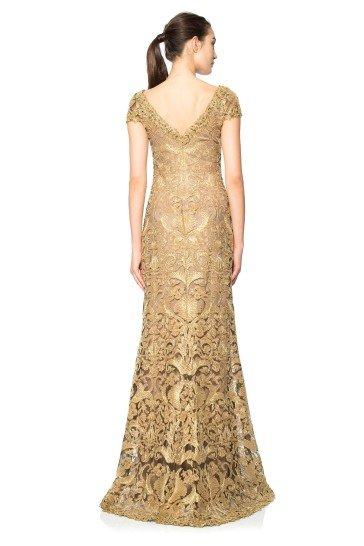 Роскошное вечернее платье прямого кроя по всей длине покрыто золотым кружевным рисунком.