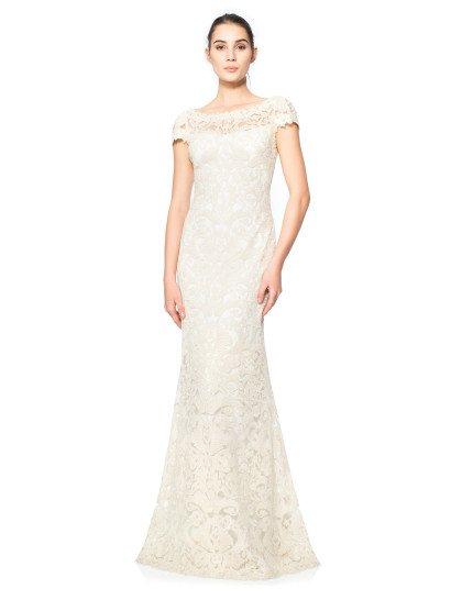 Стильное вечернее платье белого цвета полностью покрыто плотным кружевным рисунком в тон подкладки. Светлый оттенок ткани становится идеальной основой для женственного образа, а элегантный крой поддерживает настроение, создавая округлый вырез с фигурным краем и короткие рукава. Спинка вечернего платья чувственно дополнена небольшим V-образным вырезом декольте, обрамленным фактурной кружевной тканью.
