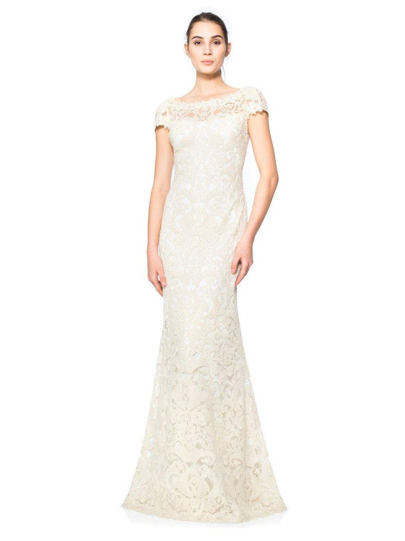Стильное вечернее платье белого цвета полностью покрыто плотным кружевным рисунком.