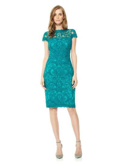 Потрясающее вечернее платье длиной до колена влюбляет яркостью ткани – бирюзово-голубая подкладка в гармоничном дуэте с верхом, украшенным синим кружевом с крупным рисунком, смотрится насыщенно и притягательно.   Фактурный кружевной верх продолжается выше прямого лифа, создавая элегантный вырез под горло с фигурным краем, а также короткие рукава прямого кроя и вставку на спинке вечернего платья.  Есть платье больших размеров.