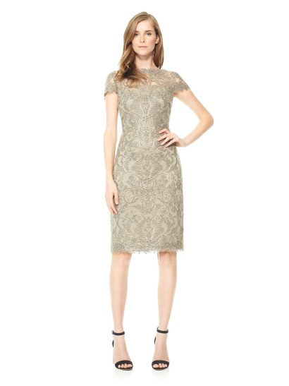 Короткое вечернее платье, выполненное в женственных бежево-золотистых тонах, обрисовывает фигуру облегающим прямым кроем. По всей длине подкладка покрыта роскошным глянцевым кружевом, абстрактный рисунок которого не просто привлекает внимание, но и украшает фигурными краями низ подола на уровне коленей, вырез лодочкой и  короткие рукава-крылышки. На спинке кружевной верх скрывает декольте прямого кроя.
