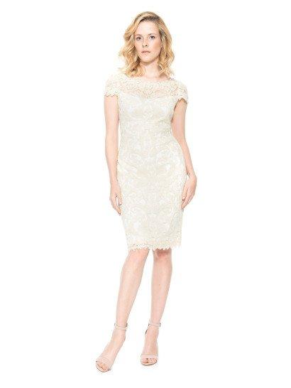 Короткое вечернее платье прямого кроя безупречно обрисовывает фигуру, а белоснежный оттенок ткани придает образу запоминающуюся элегантность и притягательность. По всей длине платье украшено кружевом в тон, над лифом прямого кроя ажурная ткань образует женственное округлое декольте, а руки украшает фигурными короткими рукавами. На спинке вечернего платья располагается изысканный V-образный вырез, обрамленный кружевом.