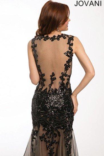 Облегающее вечернее платье выполнено из полупрозрачной ткани, украшенной аппликациями из черного кружева.