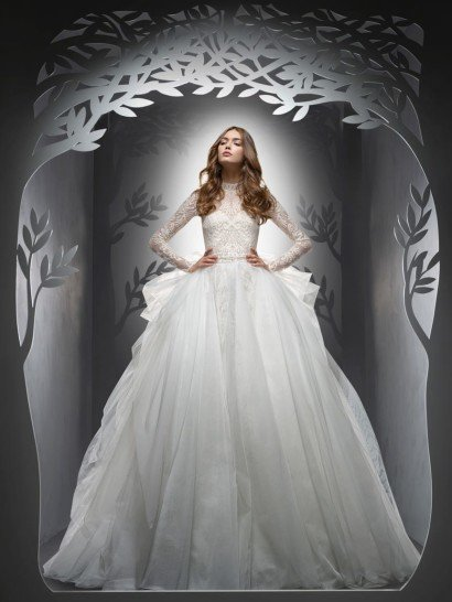 Свадебное платье-трансформер. Впечатляющая объемом многослойная юбка пышного свадебного платья украшена вертикальными складками и сложными оборками, спускающимися по подолу сзади.  Открытый корсет традиционного кроя покрыт слоем плотной ажурной ткани, которая изысканно скрывает область декольте, создавая высокий воротник и длинные облегающие рукава.  Центральным акцентом в образе служит широкий пояс с вышивкой из бисера.