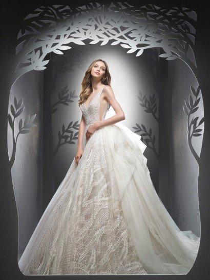 Пышное свадебное платье впечатляет юбкой, спереди украшенной кружевом с необычным растительным узором, а сзади дополненной пышными оборками из полупрозрачной ткани и объемным шлейфом.  Чувственный верх смотрится не менее притягательно – глубокие разрезы по бокам и V-образный вырез декольте сочетают в себе соблазнительность с безупречной элегантностью.  Талию помогает подчеркнуть узкий пояс с бисерной вышивкой.