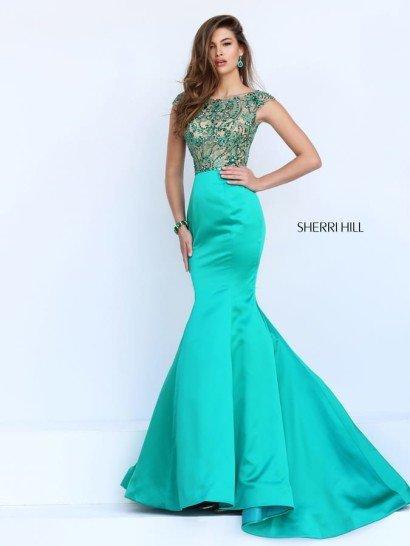 Стильное вечернее платье впечатляет силуэтом «русалка», воплощенным в роскошной атласной ткани.  Насыщенный бирюзовый оттенок становится дополнительным украшением образа.  Облегающий фигуру верх оформлен полупрозрачной тканью на бежевой подкладке.  От элегантного выреза лодочкой, обрамленного широкими бретелями, и до естественной линии талии верх вечернего платья расшит плотным слоем пайеток в тон бирюзового атласа на юбке.