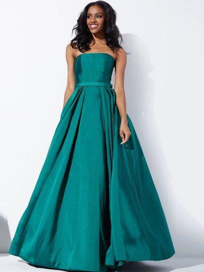 Элегантный, утонченный стиль пышного вечернего платья позволит выделиться обладательнице изысканного вкуса.  Соответствует этой задаче и глубокий изумрудный оттенок плотной ткани с глянцевой фактурой.  Изящный открытый корсет с прямым лифом дополняет сдержанный аксессуар в виде узкого атласного пояса в тон платья.  Юбку А-силуэта украшают многочисленные вертикальные складки, по бокам спускающиеся от линии талии вниз.