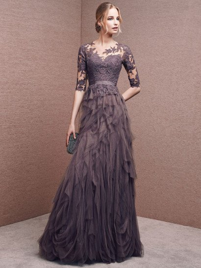 Элегантное вечернее платье притягивает взгляды сложным и глубоким оттенком ткани, прекрасно соответствующим необычному крою.  Юбку покрывают многослойные оборки полупрозрачной ткани, создающие причудливый узор по всей длине лаконичного подола прямого кроя.  Изящно подчеркнутое лифом декольте покрыто прозрачной тканью, расшитой плотным кружевным узором, романтично очерчивающим шею и покрывающим рукава длиной до локтя.