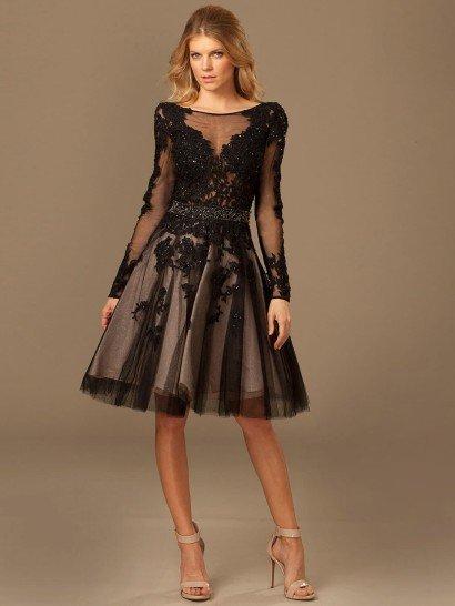 Короткое вечернее платье отличается оригинальной юбкой с полупрозрачным черным верхом и белой подкладкой, оттеняющей глянцевый кружевной декор подола.  Верх вечернего платья оформлен черной тканью с ажурными аппликациями, образующей над лифом вставку с округлым вырезом и длинными элегантными рукавами, а на спинке создающей глубокий V-образный вырез.  Талия выделена поясом, декорированным бисерной вышивкой.