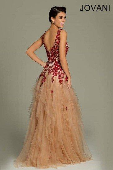 вечернее платье бежевого цвета покрыто вышивкой в черно-красных тонах.