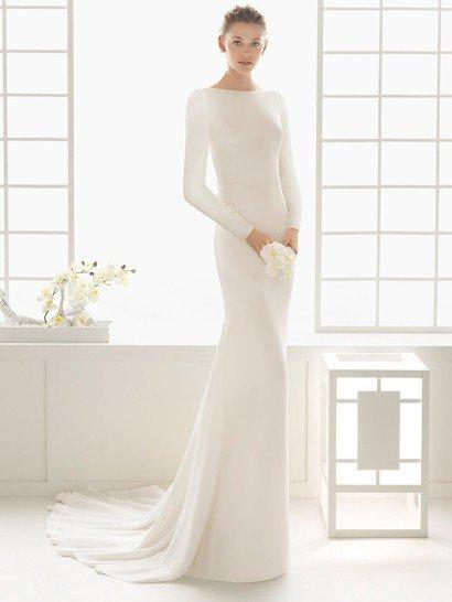 Потрясающее свадебное платье с прямым силуэтом очаровывает минималистичным стилем, который изящно подчеркивает фигуру.  Закрытый верх с вырезом лодочкой дополнен облегающими рукавами, которые украшены рядом пуговиц.  На спинке – драматичный V-образный вырез, спускающийся почти до самой линии талии.  Утонченная юбка дополнена небольшим стильным шлейфом с множеством вертикальных складок.