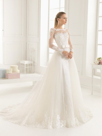 Элегантное свадебное платье оформлено над изящным лифом прямого кроя плотной ажурной тканью с абстрактным узором, дополненным выразительными крупными аппликациями, которые не только отделывают рукава, но и корсет.  На талии – стильный широкий атласный пояс с крупным прямоугольным бантом.  Юбку дополняет полупрозрачный пышный шлейф, нижний край которого покрыт фигурной полосой крупных аппликаций, повторяющих отделку корсета.