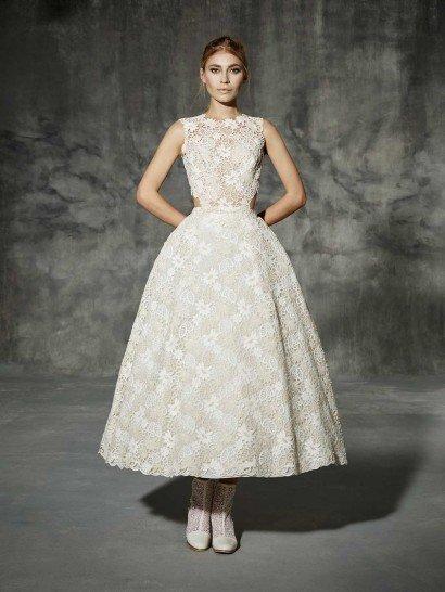 Романтичное и женственное свадебное платье создано из кружева цвета слоновой кости, очаровывающего красивейшим цветочным узором.  Подкладка верха создает иллюзию прозрачности, а юбка выполнена из более плотной ткани.  Элегантную юбку чайной длины и закрытый верх с округлым вырезом и широкими фигурными бретелями смело дополняет актуальный тренд на вырезы на уровне линии талии, сзади открывающие спину.  Свадебные платья Yolan Crisэксклюзивно представлены в салоне Виктория  Примерка платьев Yolan Cris —платная