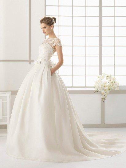 Пышное свадебное платье с длинным шлейфом дополнено несколькими характерными для бренда деталями – это стильный атласный пояс с деликатным бантом спереди и скрытые в вертикальных складках ткани на подоле карманы.  Открытый корсет с изящным вырезом декольте от талии покрыт полупрозрачной кружевной тканью, она создает короткие фигурные рукава облегающего кроя, а на спинке обрисовывает глубокий V-образный вырез.