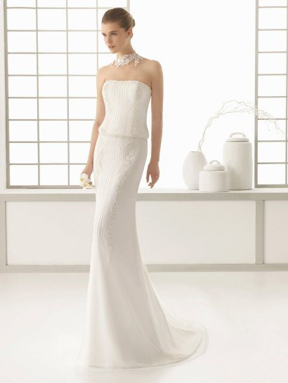 Свадебное платье с элегантным открытым лифом прямого фасона.  Платье отличает необычное оформление линии талии и интересная отделка.  Край линии декольте оформлен вышивкой, по корсету и сдержанной юбке спускаются фактурные вертикальные полосы кружевного узора и изящной тесьмы.  Кроме того, юбка свадебного платья дополнена полупрозрачной тканью, которая сзади становится чуть длиннее, образуя романтичный шлейф.