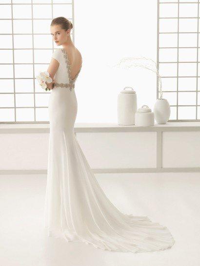 Изысканный крой прямого свадебного платья, воплощенного в креповой ткани, облегает силуэт и создает торжественную атмосферу сдержанным шлейфом, спускающимся сзади от уровня коленей узкими вертикальными складками.  Яркой деталью служит V-образное декольте на спинке платья, обрамленное широкой полосой блестящей вышивки из бисера.  Такая же вышивка служит и альтернативой поясу в качестве акцента на талию невесты.