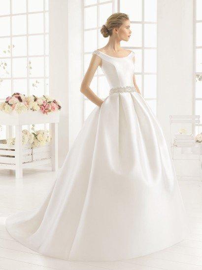 Великолепное свадебное платье с пышной юбкой выполнено из сияющего шелка микадо, который дополнен вышивкой из бисера, широкой полосой располагающейся по талии и украшающей спинку с эксцентричным глубоким вырезом, дополненным двумя крупными шелковыми бантами.  Юбка украшена не только выразительными вертикальными складками ткани, но и длинным шлейфом, а по бокам ее стильно дополняют скрытые карманы.