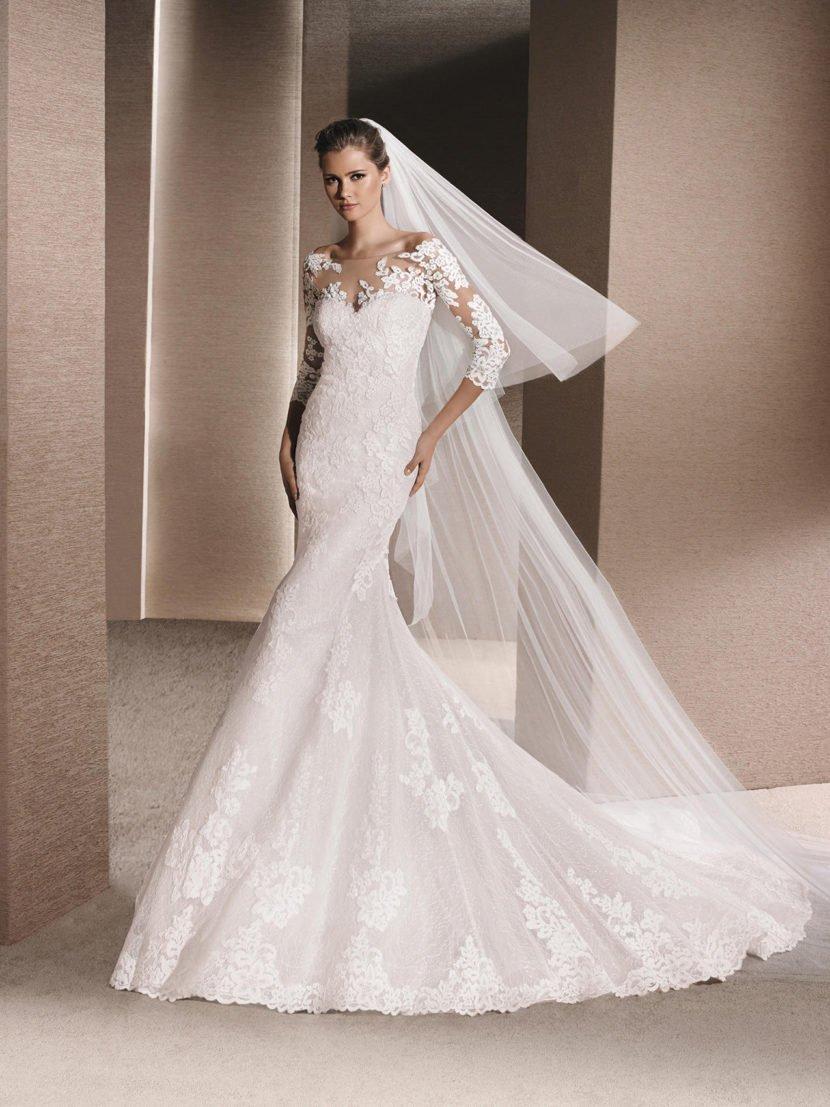 Закрытое свадебное платье с силуэтом «русалка», покрытое кружевным декором.