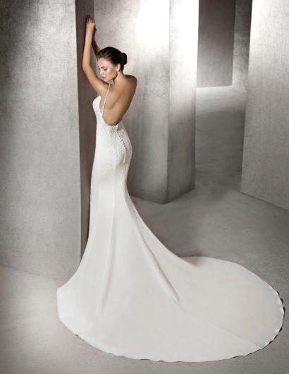 Изысканное свадебное платье с облегающим кроем и отделкой из кружевной ткани.
