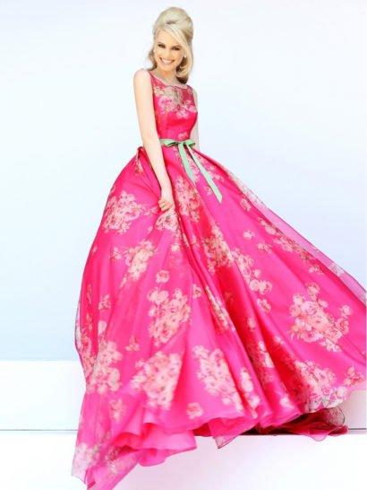Пышное выпускное платье насыщенного розового цвета декорировано рисунком из мелких светло-розовых бутонов. Закрытый верх с элегантным вырезом бато красиво подчеркивает форму шеи, а на талии в качестве акцента располагается узкий атласный пояс пастельного зеленого оттенка. Многослойная ткань юбки создает особенный торжественный объем, который делает настроение выпускного платья ярким и незабываемым.