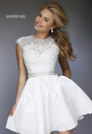 Короткое выпускное платье цвета слоновой кости с декором из кружева и стразов.