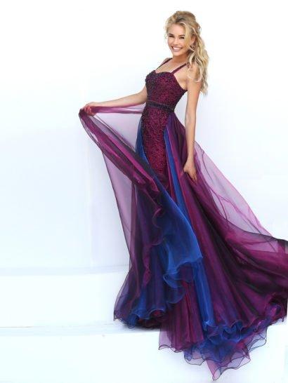 Впечатляющая игра красок на юбке выпускного платья создана несколькими слоями шифона фиолетового и синего цветов, располагающимися по подолу прямого кроя сзади. Облегающий верх с лифом в форме сердца дополнен узкими бретелями из плотной ткани. По всей длине выпускное платье покрыто вышивкой из черных бусин и бисера такого же цвета, создающей выразительную фактуру, оттеняющую фиолетовый оттенок ткани.