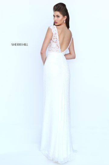 Прямое выпускное платье белого цвета с кружевной отделкой и атласным поясом.