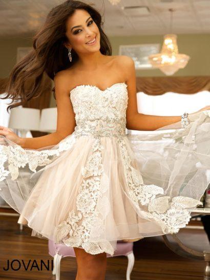 Короткое выпускное платье с пышной юбкой длиной до середины бедра выполнено из ткани бежевого оттенка, идеально оттеняющего крупные кружевные аппликации, вертикальными полосами спускающиеся по подолу. Открытый лиф корсета полностью покрыт кружевом, оно делает край выреза фигурным. На линии талии кружевную отделку деликатно дополняет серебристая вышивка из бисера, проходящая широкой горизонтальной полосой.