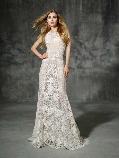 Богемный стиль придает прямому силуэту закрытого свадебного платья выразительный характер – по всей длине платье покрыто кружевными узорами и аппликациями. По бокам располагаются ажурные вставки с узором в клетку, а по середине проходит крупный цветочный узор, который особенно выделяется на полупрозрачной юбке. Низ подола – фигурный, сзади юбка складывается в шлейф из кружев. Линию талии вместо пояса выделяет горизонтальная полоса узора.