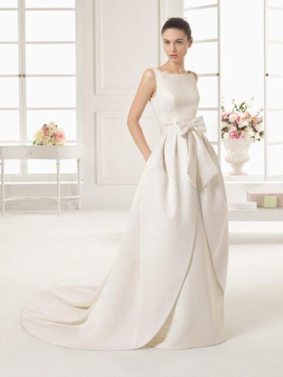 Свадебное платье впечатляет необычной верхней юбкой, спускающейся от широкого атласного пояса с пышным бантом спереди.  Юбка делает силуэт объемным и создает длинный шлейф, без него платье становится прямым и лаконичным.  Верх свадебного платья тоже выполнен в лаконичном стиле – он очерчивает линию шеи вырезом лодочка, а главным украшением образа становится глубокое округлое декольте, расположенное на спинке.