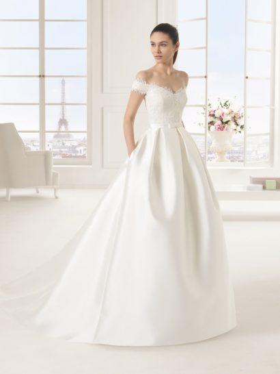 Стильное портретное декольте, украшающее корсет пышного свадебного платья, оформлено по краю ажурной тканью.  Кружево, декорированное бисерной вышивкой, спускается от выреза вниз, доходя до линии талии, очерченной узким поясом из атласа.  Драматичная красота пышной юбки с длинным шлейфом подчеркнута стильными вертикальными складками по верхней части подола, а также оригинальными скрытыми карманами по бокам.