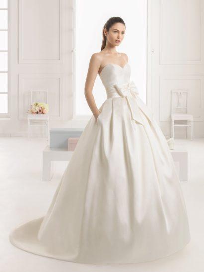 Стильное и роскошное свадебное платье с пышным силуэтом соблазнительно окутывает фигуру сияющей тканью.  Область декольте женственно очерчена открытым лифом в форме сердечка, а на талии располагается широкий пояс со складками и объемным бантом.  Юбку с длинным глянцевым шлейфом декорируют вертикальные складки, идущие от пояса по верху подола, и скрытые в них карманы по бокам.  Преобразить платье можно ажурным верхом, скрывающим декольте.