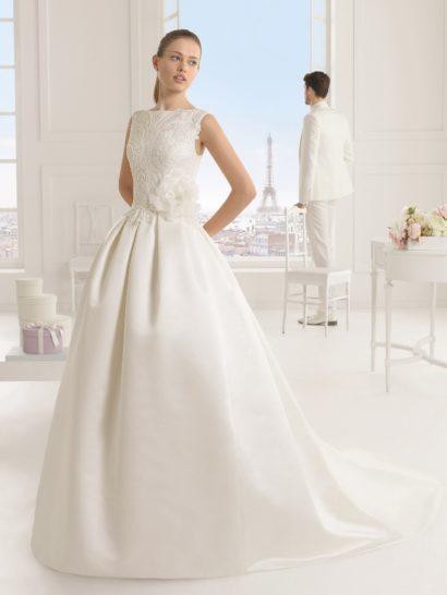 Пышное свадебное платье с длинным шлейфом сзади дополнено выразительным кружевным узором – ажурная ткань покрывает закрытый верх с вырезом лодочкой и служит вставкой в области декольте на спинке, открытой округлым вырезом.  На уровне талии платье украшено пышным бутоном с полупрозрачными лепестками, а верхнюю часть подола декорируют крупные вертикальные складки плотной ткани.