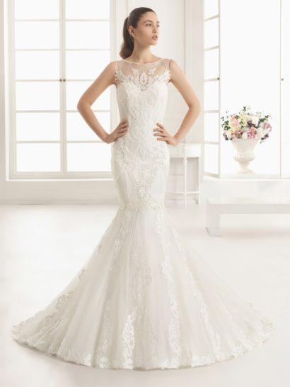 Классическое свадебное платье с силуэтом «русалка» покрыто слоем ажурной ткани с рисунком в мелкий горошек, она обрисовывает шею округлым вырезом и создает широкие бретели.  По всей длине тонкую ткань покрывают крупные кружевные аппликации, украшающие декольте над лифом и на спинке платья, скрывающие корсет и вертикальными полосами проходящие по многослойной юбке, переходящей в великолепный объемный шлейф сзади.
