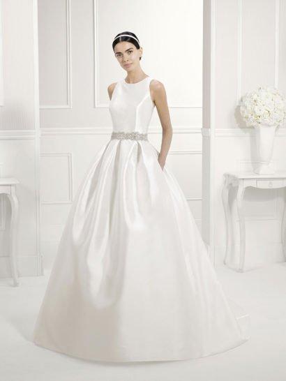 Пышное свадебное платье из плотного глянцевого атласа с элегантным закрытым верхом изящно подчеркивает форму плеч и шеи округлым вырезом с узкими бретелями, а спинку открывает смелым вырезом, на котором бретели перекрещиваются.  Талия выделена фигурным поясом, декорированным бисерной вышивкой.  Пышная юбка, оформленная крупными складками у талии, переходит сзади в шлейф, ее стильным дополнением служат скрытые карманы.