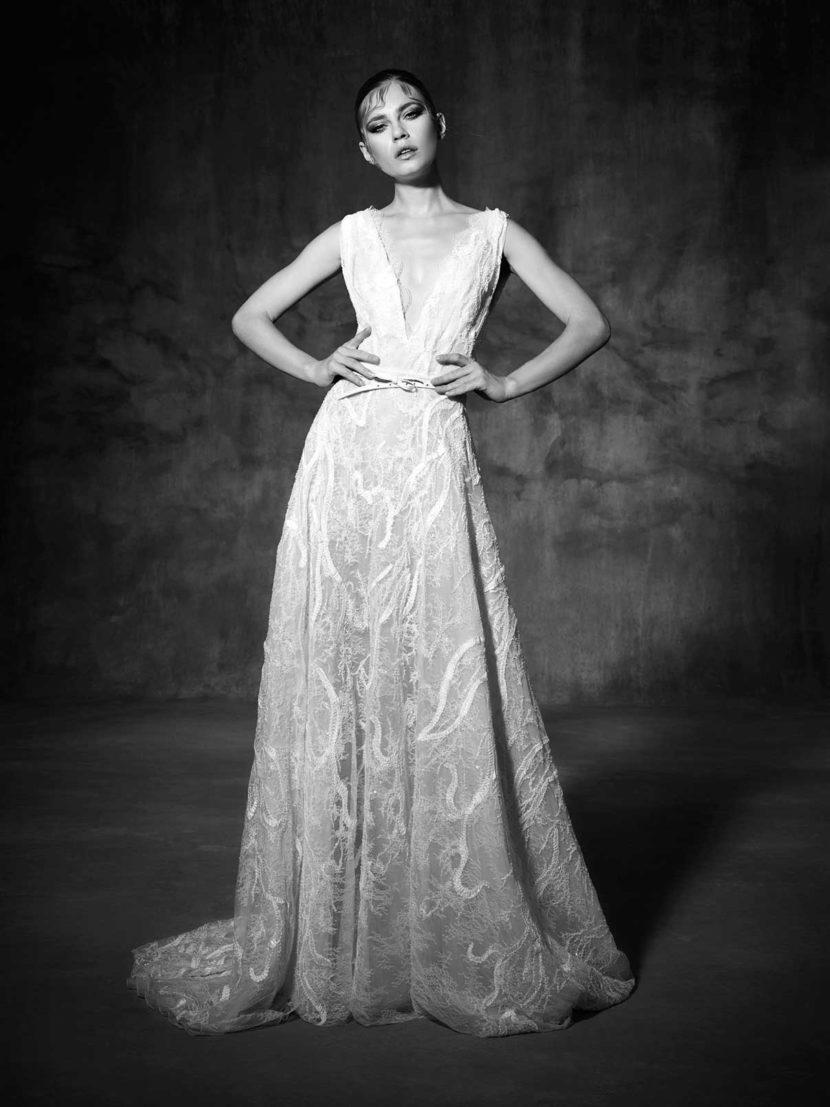 Свадебное платье с глубоким V-образным вырезом, выполненное из фактурного кружева.