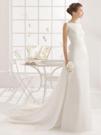 Идеальная элегантность линий свадебного платья А-силуэта покорит утонченную невесту.  Закрытый спереди лиф с вырезом бато сзади открывает спинку глубоким округлым декольте.  Область талии сдержанно подчеркнута широкой горизонтальной полосой кружевной отделки.  На спинке – пышный атласный бант, от которого вниз спускаются выразительные складки ткани, плавно переходящие в волну шлейфа.  Свадебное платье 2016 года