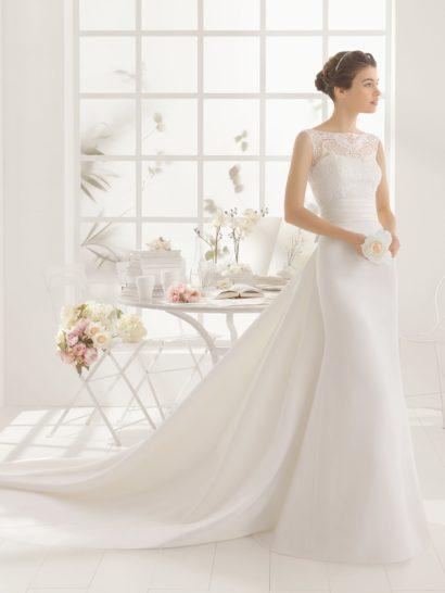 Соблазнительный силуэт свадебного платья «русалка» дополняет потрясающий длинный шлейф, спускающийся сзади от самой линии талии вниз несколькими лаконичными волнами плотной ткани. Выделить талию помогает широкий пояс, покрытый горизонтальными драпировками и завязанный бантом. Открытый лиф укрыт полупрозрачной белой вставкой с кружевным рисунком, обрамляющим шею по краям округлого выреза и украшающим спинку платья.