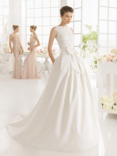 Закрытое свадебное платье с пышным силуэтом, подчеркнутым плотными вертикальными складками ткани по верху подола, смотрится женственно и празднично.  На талии выделяется эксцентричный аксессуар – очень широкий пояс, спереди завязанный крупным бантом.  Верх с вырезом бато без рукавов от талии до шеи покрыт вышивкой из белого бисера.  Спинка платья открыта глубоким V-образным вырезом.