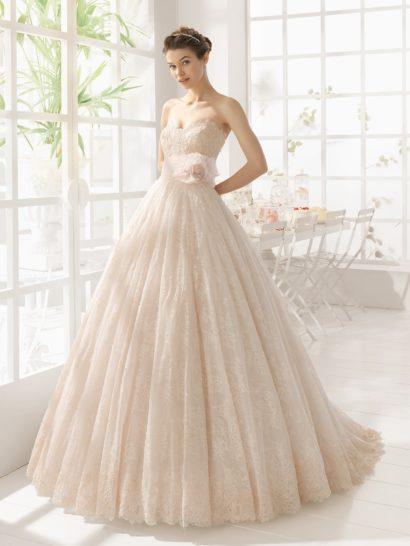 Изысканный бежевый оттенок и кружевная отделка по всей длине делают открытое свадебное платье с пышным силуэтом невероятно романтичным. На талии располагается широкий пояс из полупрозрачной ткани в тон, украшенный сбоку пышным цветочным бутоном. По всей длине ажурный декор дополнен бисерной вышивкой. Образ можно использовать и в закрытом варианте, дополнив открытый лиф кружевным болеро с облегающими рукавами и округлым вырезом.