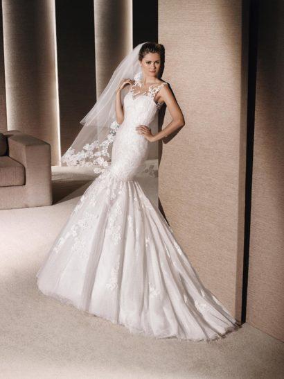 Романтичное свадебное платье с роскошной юбкой силуэта «русалка» по всей длине оформлено кружевом.  Ажурные аппликации продолжаются над лифом по прозрачной основе, создавая эфемерные фигурные бретели, они же обрамляют глубокий округлый вырез на спинке свадебного платья.  При желании, образ можно преобразить – нижняя часть подола с длинным шлейфом снимается, превращая свадебное платье в стильный короткий наряд длиной чуть выше колена.