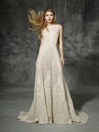 Прямое свадебное платье выполнено из плотной ажурной ткани на подкладке в тон кожи, что создает невероятно соблазнительный, впечатляющий смелостью образ.  Геометрический узор ткани дополняют крупные аппликации с цветочным мотивом, обрамляющие как округлый вырез закрытого верха и линию талии, так и нижнюю часть подола юбки.  Мягкими волнами юбка сзади переходит в торжественный шлейф с фигурным краем по всей длине.  Свадебные платья Yolan Crisэксклюзивно представлены в салоне Виктория  Примерка платьев Yolan Cris —платная