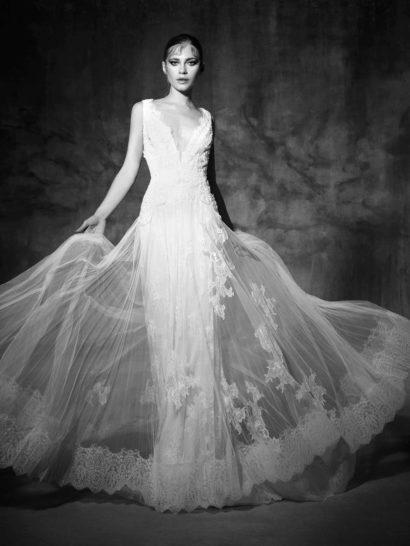 Невероятно красивое свадебное платье с изящным прямым силуэтом стильно открывает область декольте глубоким V-образным вырезом, обрамленным симметричными бретелями, покрытыми объемными кружевными аппликациями.  Стильную юбку из плотной ткани покрывает роскошный полупрозрачный верх более просторного кроя с шлейфом сзади, украшенный романтичными аппликациями и широкой ажурной полосой по нижнему краю подола.  Свадебные платья Yolan Crisэксклюзивно представлены в салоне Виктория  Примерка платьев Yolan Cris —платная