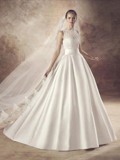 Атласное свадебное платье с пышным силуэтом превосходно справляется с созданием неповторимой торжественной атмосферы.  Крупные складки ткани струятся по юбке от талии, сзади подол дополнен полукругом шлейфа.  Открытый атласный корсет с традиционной формы лифом покрыт кружевной отделкой, скрывающей область декольте, покрывающей спинку платья и создающей фигурный округлый вырез, очерчивающий шею.