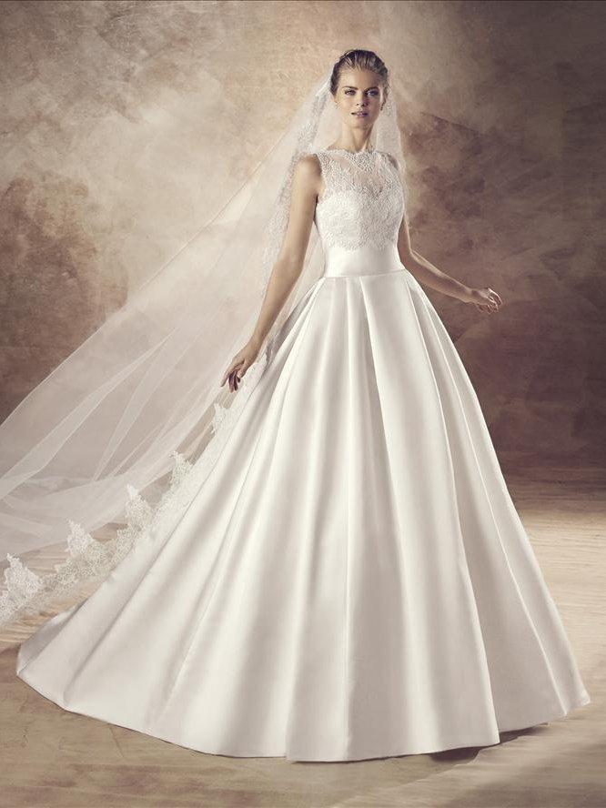 Пышное свадебное платье из атласной ткани с кружевной вставкой на лифе.