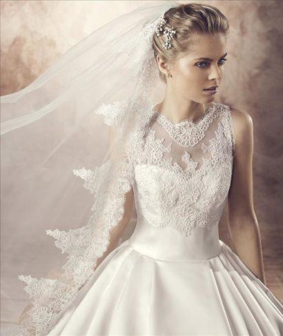 Пышное свадебное платье и атласной ткани с кружевной вставкой на лифе.