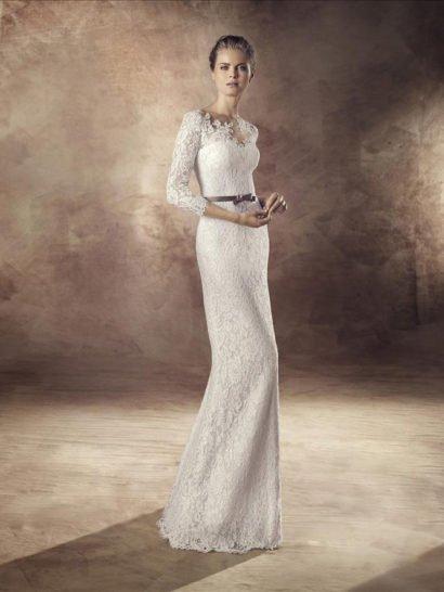 Деликатный прямой силуэт красиво подчеркивает фигуру. Кружевная ткань, плотным фактурным слоем покрывающая свадебное платье по всей длине, акцентирует лаконичные особенности кроя. Элегантный открытый лиф в форме сердца дополнен плотным кружевом, создающим фигурное V-образное декольте и прямого кроя рукава длиной в три четверти. В роли аксессуара используется узкий атласный пояс темного лилового оттенка, завязанный бантом.