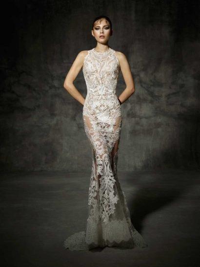 Прозрачная ткань свадебного платья с силуэтом «русалка» придает образу подчеркнуто чувственное настроение.  Крупный рисунок кружевных аппликаций, использованных для отделки по всей длине, акцентирует изгибы фигуры и смотрится невероятно привлекательно.  При этом, платье сдержанно закрывает декольте высоким вырезом под горло. Низ юбки со шлейфом сзади полностью прозрачный, лишь по краю подола – широкая ажурная полоса.  Свадебные платья Yolan Crisэксклюзивно представлены в салоне Виктория  Примерка платьев Yolan Cris —платная